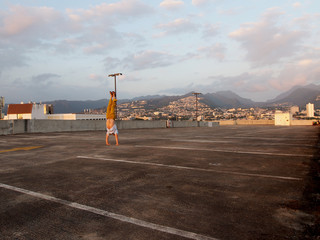 Man does Handstand on top floor of parking garage with City of Honolulu in distance