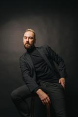 Elegant handsome man in classical suit poses in studio theatre.