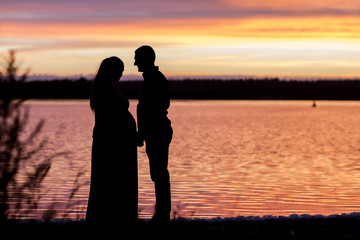 Man and woman portrait silhouettes of happy young couple looking at each other and smiling outdoor
