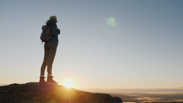 Crane shot: A woman traveler stands on top of a mountain, looks at the beautiful landscape ahead, admires the nature of Norway