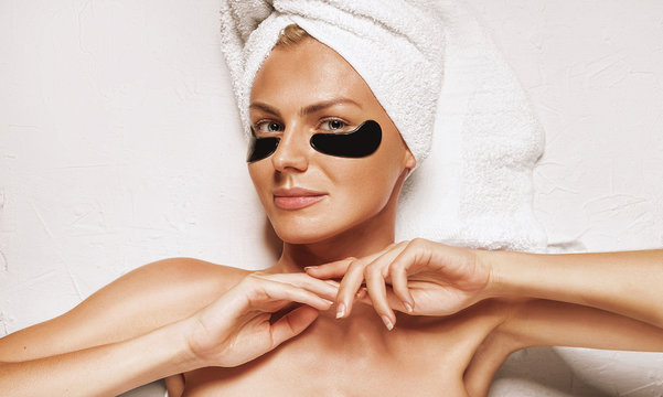 cosmetic mask for the skin under the eyes. patch eye mask on a girl with a towel on her head