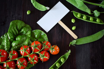 Cherry tomatoes, chard and green peas are framing an empty card in the middle against the dark background. Copy space