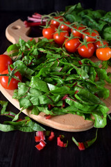 Chopped chard leaves on a cutting board and cherry tomatoes next to it