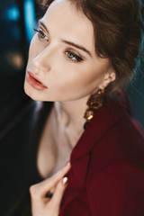 Portrait of sensual, fashionable and beautiful brunette model girl with bright professional makeup and with earrings, in red jacket posing at interior
