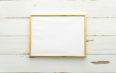 Golden photo frame for painting or picture on white wooden background. Flat lay, top view. Horisontal mockup