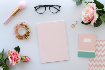 women accessories including blank paper for lettering, notepad, black glasses and roses on white background. beauty concept. Pink color composition, top view