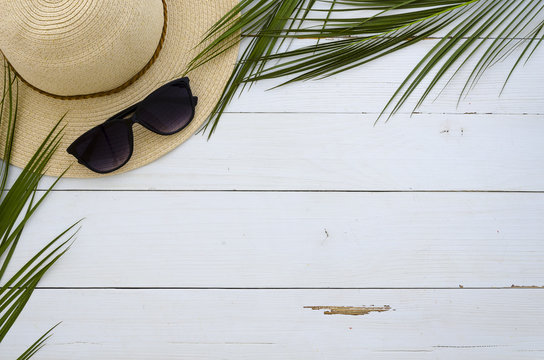 Summer vacation, travel, holiday, beach concept. Sun hat, sunglasses and tropical palm leaves on white wooden board. Top view, space for text. Flat lay mock up