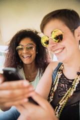 Two young mixed women having fun using a smartphone.