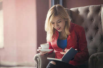Young blonde woman reading a book inside a lovely coffee shop