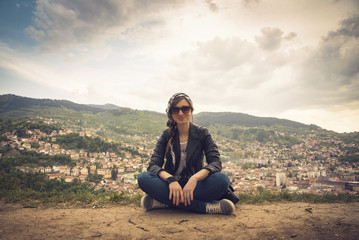 Young casual woman sitting on top of a hill, her back turned to the background of the city Sarajevo in Bosnia