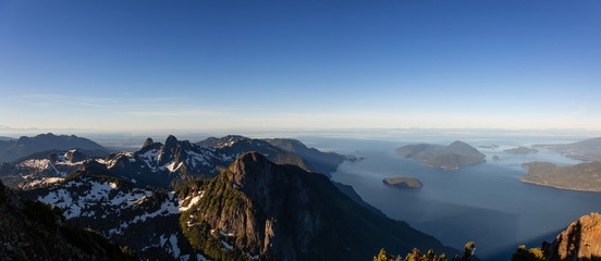 Panoramic landscape view of Howe Sound during a vibrant summer sunrise. Taken from the top of Brunswick Mountain, North of Vancouver, BC, Canada.