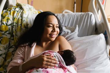 Woman feeding newborn daughter in hospital