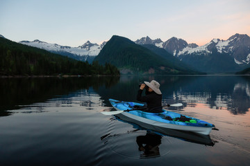 Adventure photographer on a kayak in the water surrounded by the Beautiful Canadian Mountain Landscape. Taken in Jones Lake, near Hope, East of Vancouver, BC, Canada.