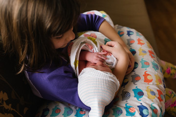 Sister bonding with newborn brother