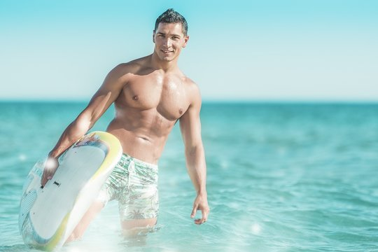 Surfer beach lifestyle people - man surfing running with with