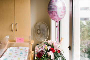 Baby girl balloon and flowers in hospital