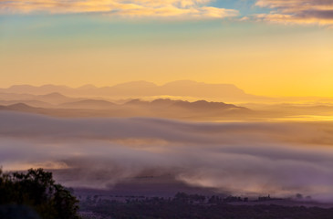 Mountain ridges protruding above low clouds at vivid sunset in Australia