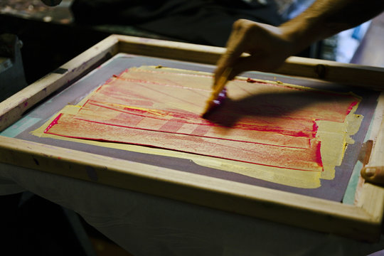 Silkscreening hand with squeegee.