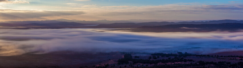 Large panorama of Flinders Ranges mountains covered in low clouds at sunrise in South Australia