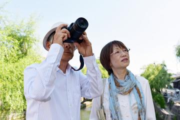 旅先の観光地でカメラを構えるシニア夫婦