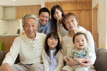 リビングのソファで微笑む3世代家族