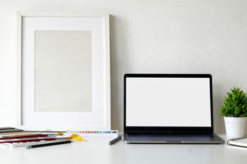 Mockup blank screen laptop and poster on white desk. Graphic display montage