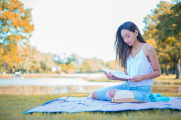 Young woman relaxing in the natural park. Vacation on Autumn season.