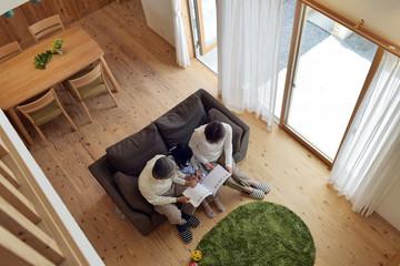 リビングで孫と絵本を読む祖父母・俯瞰