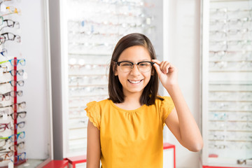Cheerful girl deciding to buy new spectacles in optician store with eyewear in display in background