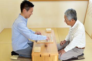 和室で将棋を楽しむシニア男性と若い男性