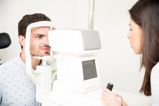 Young optometrist with autorefractor checking man patient at eye clinic