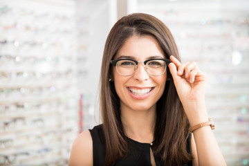 Customer in optician's shop choosing the right frame for eyeglasses