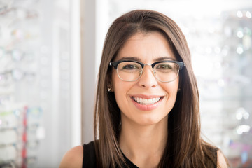 Smiling latin woman trying new eyeglasses for daily purpose in optical store