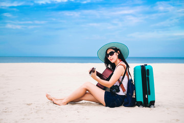 Woman traveler sitting on a baggage and playing a guitar on the beach during holiday.