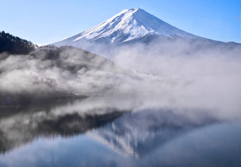 Mount Fuji reflection in calm lake in the early morning. Iconic mountain with snow on top and reflection in calm water.  Silhouettes of trees and hills in the mist.  Lake Kawaguchiko. Japan.