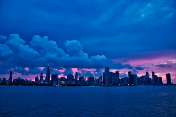 Sunset over city of Chicago skyline during evening, seen from Lake Michigan in summer boat ride.