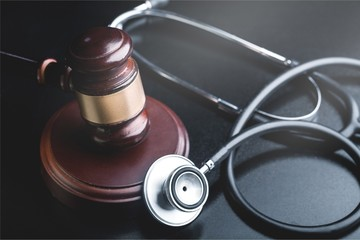 Wooden gavel and stethoscope on wooden background