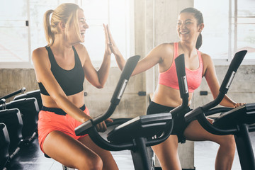 Attractive young women working out together on exercise bike at the gym.