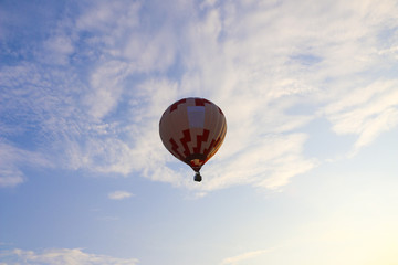 colorful hot air balloon against blue sky. hot air balloon is flying in white clouds. beautiful flying on hot air balloon
