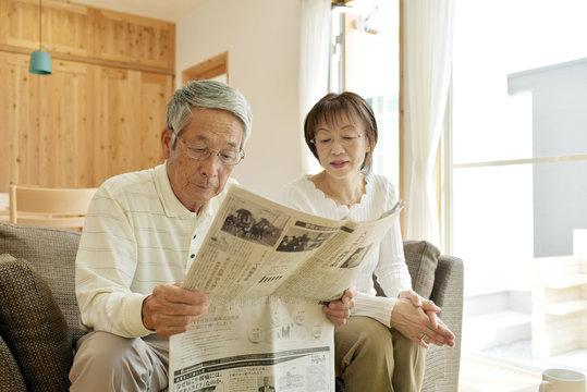 リビングのソファで新聞を読むシニア夫婦
