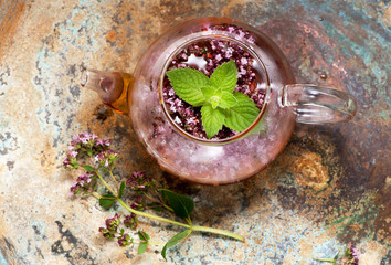 Herbal tea with mint and oregano in a glass teapot