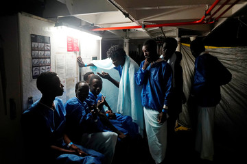 Migrants rest on board the NGO Proactiva Open Arms rescue boat in the central Mediterranean Sea