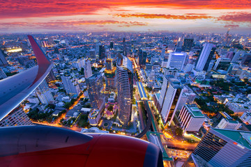 Travel transportation concept by Airplane is flying over Bangkok city skyline with beautiful landscape during at dusk.