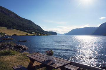 A table with a flower arrangement stands on the shore of the fjord in Norway on a summer day