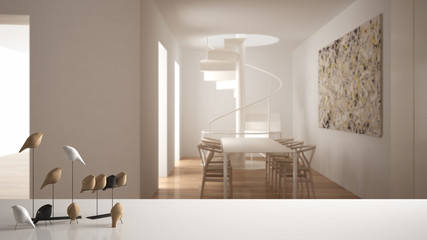 White table top or shelf with minimalistic bird ornament, birdie knick - knack over blurred contemporary living room with dining table and spiral staircase, modern interior design