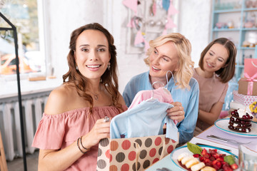 Opening presents. Appealing anticipating woman opening presents for her baby while sitting in bakery with friends