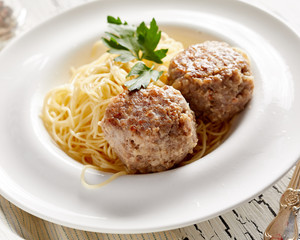 Pasta with two cutlets on rustic white table