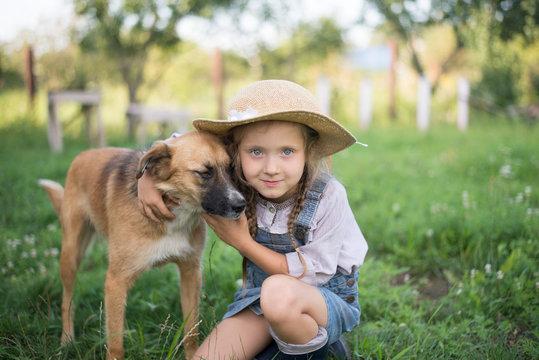 Girl and dog playing during autumn gardening in yard