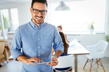 Portrait of handsome male manager using digital tablet