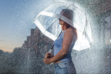 Woman in blue jeans in the rain with transparent umbrella at night. Sad young woman in the rain with umbrella in the evening. Beautiful woman with a transparent umbrella in the lanterns and rain drop